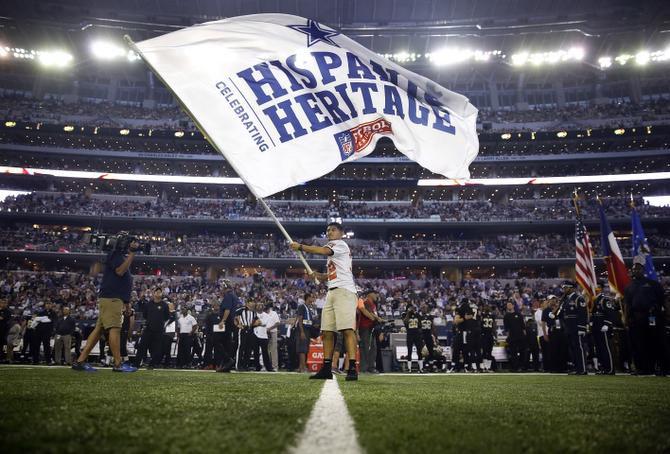 Luis Chaparro, jugador del equipo de futbol americano de la preparatoria North Dallas portó una bandera con el mensaje del Mes de la Herencia Hispana durante el partido entre los Cowboys de Dallas y los Saints de New Orleans en el AT&T Stadium de Arlington en 2018.