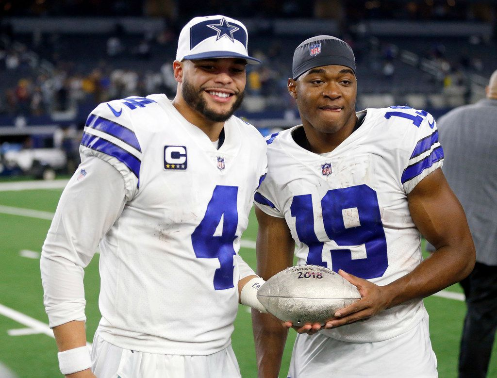 Dallas Cowboys quarterback Dak Prescott (4) and Dallas Cowboys wide receiver Amari Cooper (19) share the FOX Sports Thanksgiving football award following their win over the Washington Redskins at AT&T Stadium in Arlington, Texas, Thursday, November 22, 2018. The Cowboys defeated the Redskins, 31-23. (Tom Fox/The Dallas Morning News)