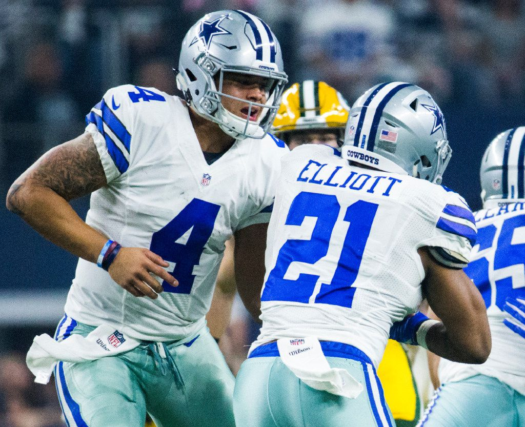 Dallas Cowboys quarterback Dak Prescott (4) hands the ball off to Dallas Cowboys running back Ezekiel Elliott (21) during the first quarter of their divisional playoff game against the Green Bay Packers on Friday, January 15, 2017 in Arlington, Texas. (Ashley Landis/The Dallas Morning News)
