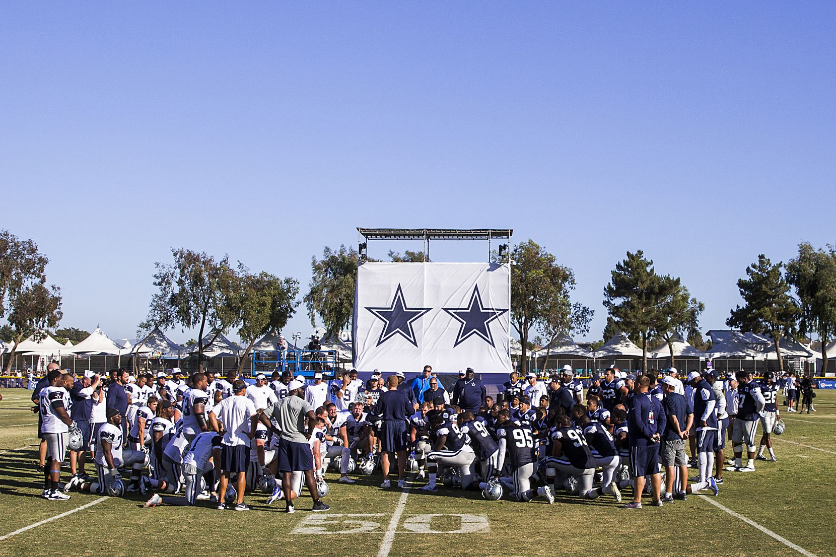 Dallas Cowboys players huddle around head coach Jason Garrett at the conclusion of afternoon practice at training camp on Tuesday, Aug. 4, 2015, in Oxnard, Calif. (Smiley N. Pool/The Dallas Morning News)