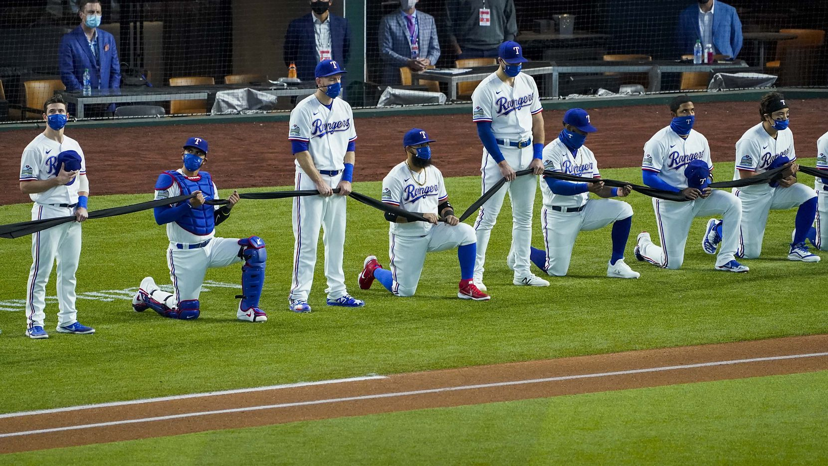 Texas Rangers players alternately stand or kneel while holding a black fabric before the singing of the national before playing the Colorado Rockies on opening day at Globe Life Field on Friday, July 24, 2020.