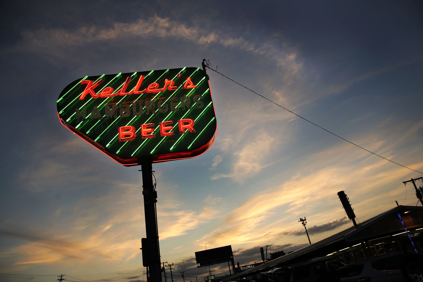 The sun sets behind Keller's Drive-In's neon sign.