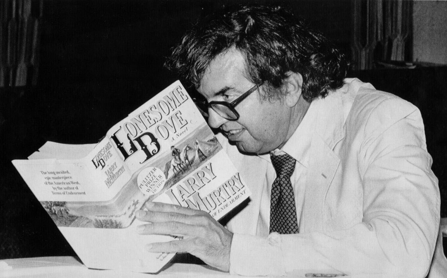 Pulitzer prize winning author Larry McMurtry autographs a copy of one of his books, Lonesome Dove, during a 1986 visit to North Texas State University (now UNT) in Denton, before speaking about Texas novels.