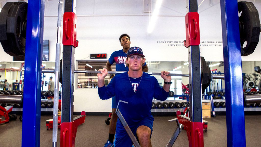 Texas Rangers' pitcher Mason Englert (front) squats with the help of teammate Destin Dotson (rear) at the Rangers' training facility Thursday, Aug. 9, 2018 in Surprise, Arizona. Englert and Dotson and other pitchers are learning from a program that is designed to hopefully prevent injury.(Darryl Webb/Special Contributor)