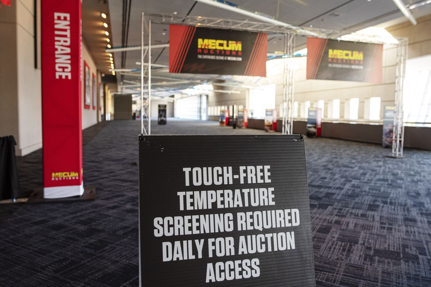 Before entering the main hall of the Kay Bailey Hutchison Convention Center for the Mecum Auto Auction, visitors will have daily temperature screenings.