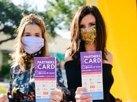 Partners Card 2020 chairs, Sally Pretorius Hodge, left, and Lexie Aderhold, right, pose with their paper cards. The discount card is also available in mobile form. The annual shopping fundraiser for The Family Place is Oct. 30 through Nov. 8. Partners Cards cost $75 and give shoppers 20% off on purchases at 550 participating stores and websites.