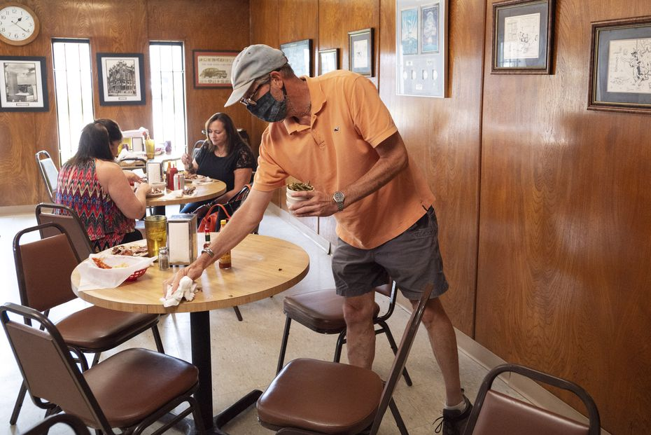 """Customer Pat Bywaters lends a hand by cleaning tables after eating lunch at Mac's Bar-B-Que in Dallas. """"Not many places these days do [barbecue] like he does. He does it the traditional way,"""" Bywaters says."""