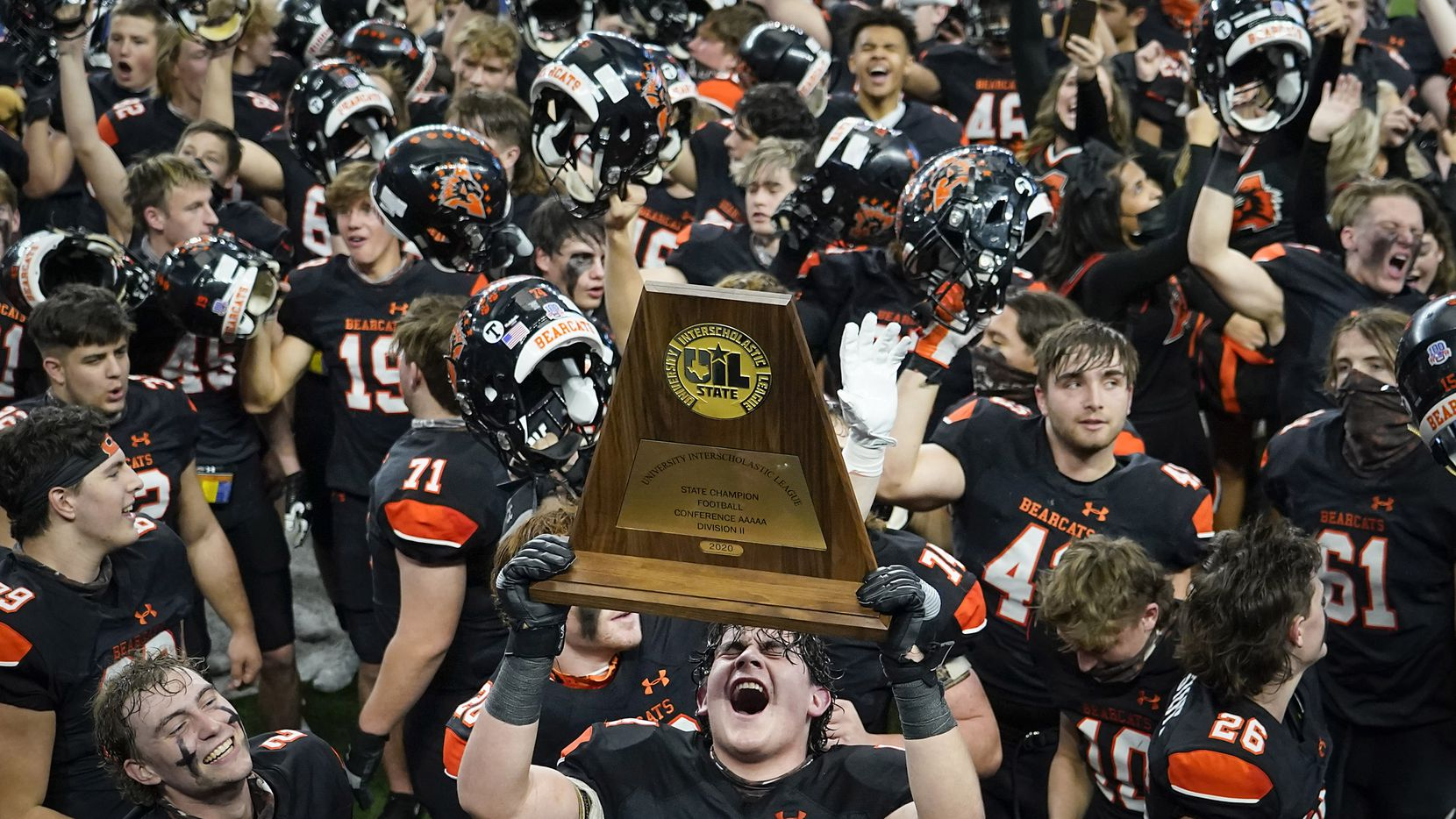 Aledo offensive lineman Rocco O'Keefe (54) hoists the championship trophy as the Bearcats  celebrate after a 56-21 victory over Crosby to win the Class 5A Division II state football championship game at AT&T Stadium on Friday, Jan. 15, 2021, in Arlington. The victory gave Aledo the 10th state championship in school history.