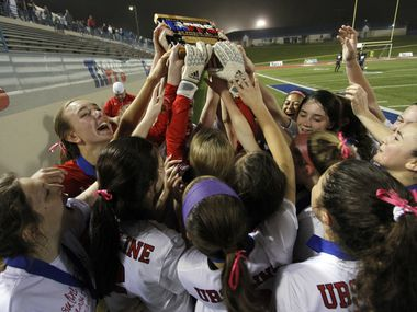 Ursuline players stretch to reach the state championship trophy they were awarded following their 2-0 victory over John Paul ll. The two teams played their TAPPS Division 1 girls state soccer championship game at Waco ISD Stadium in Waco on February 23, 2018.