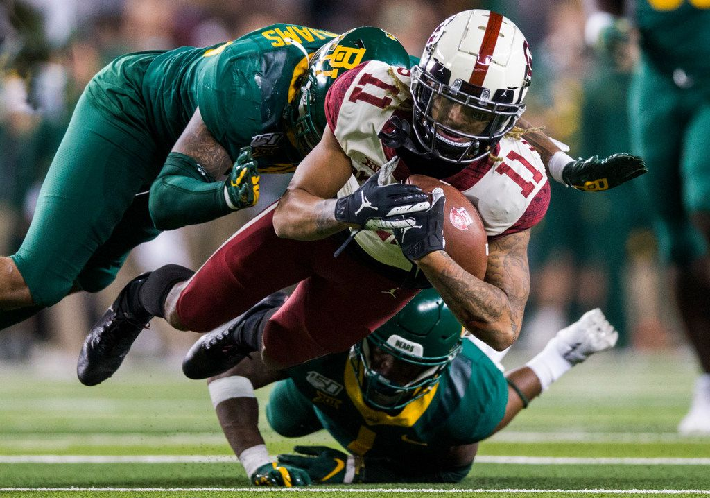Oklahoma Sooners wide receiver Jadon Haselwood (11) is tackled by Baylor Bears cornerback Grayland Arnold (1) and linebacker Jordan Williams (38) during the fourth quarter of an NCAA football game between Baylor University and Oklahoma University on Saturday, November 16, 2019 at McLane Stadium in Waco, Texas. (Ashley Landis/The Dallas Morning News)