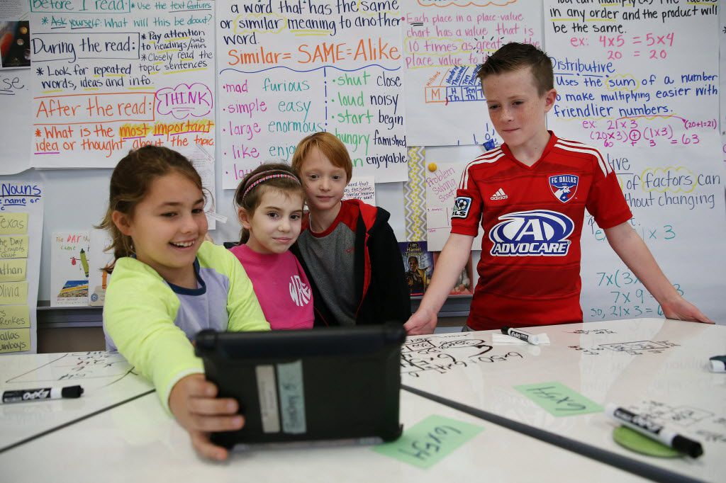 Students take a selfie with a tablet after working on a mathematics equation in a third grade class taught by Grace Hanchey at White Rock Elementary, a Richardson Independent School District school, in 2015.