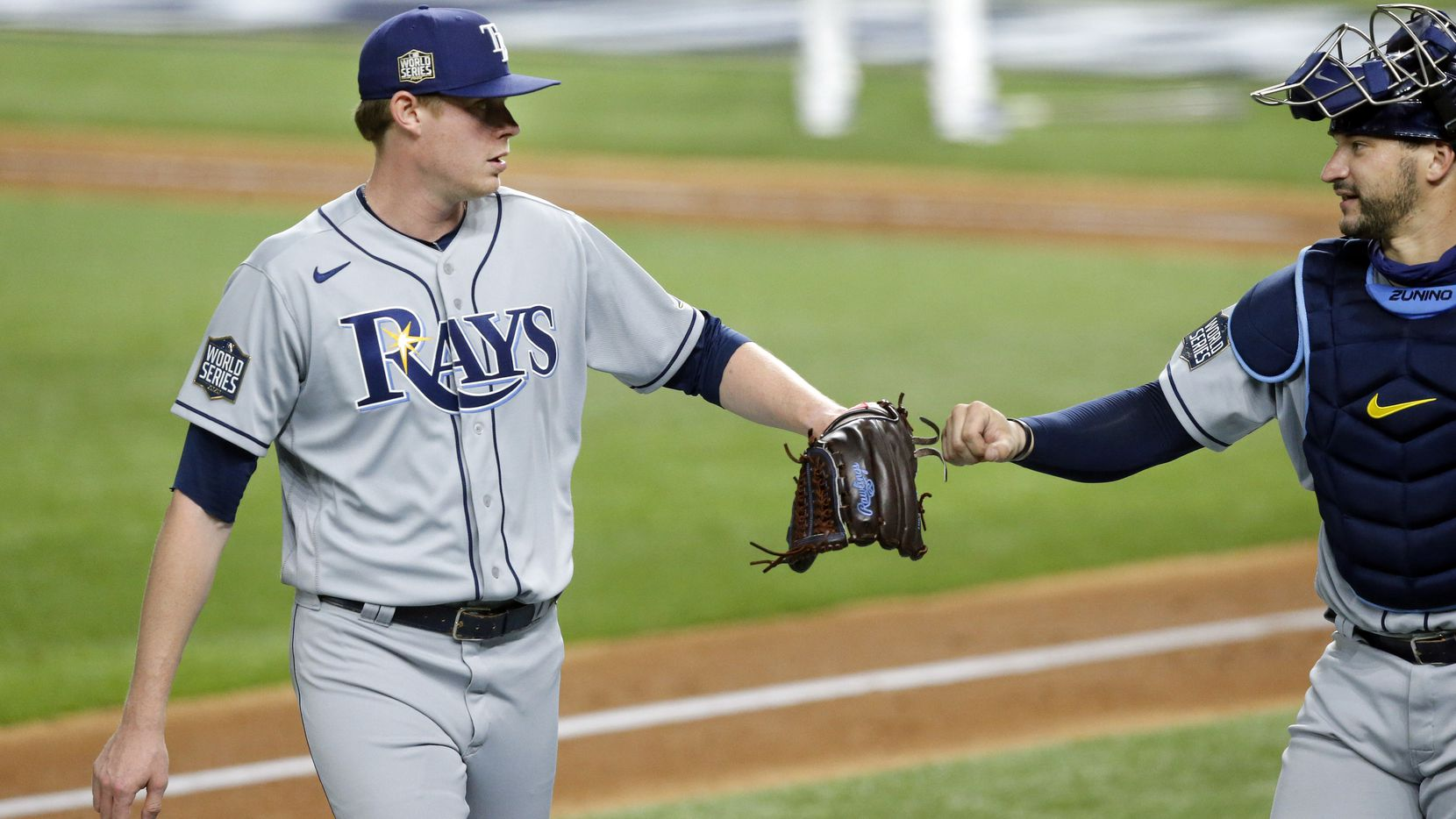Tampa Bay Rays relief pitcher Peter Fairbanks (29) receives a fist bump from catcher Mike Zunino (10) after getting out of the seventh inning against the Los Angeles Dodgers in Game 2 of the World Series at Globe Life Field in Arlington, Wednesday, October 21, 2020.