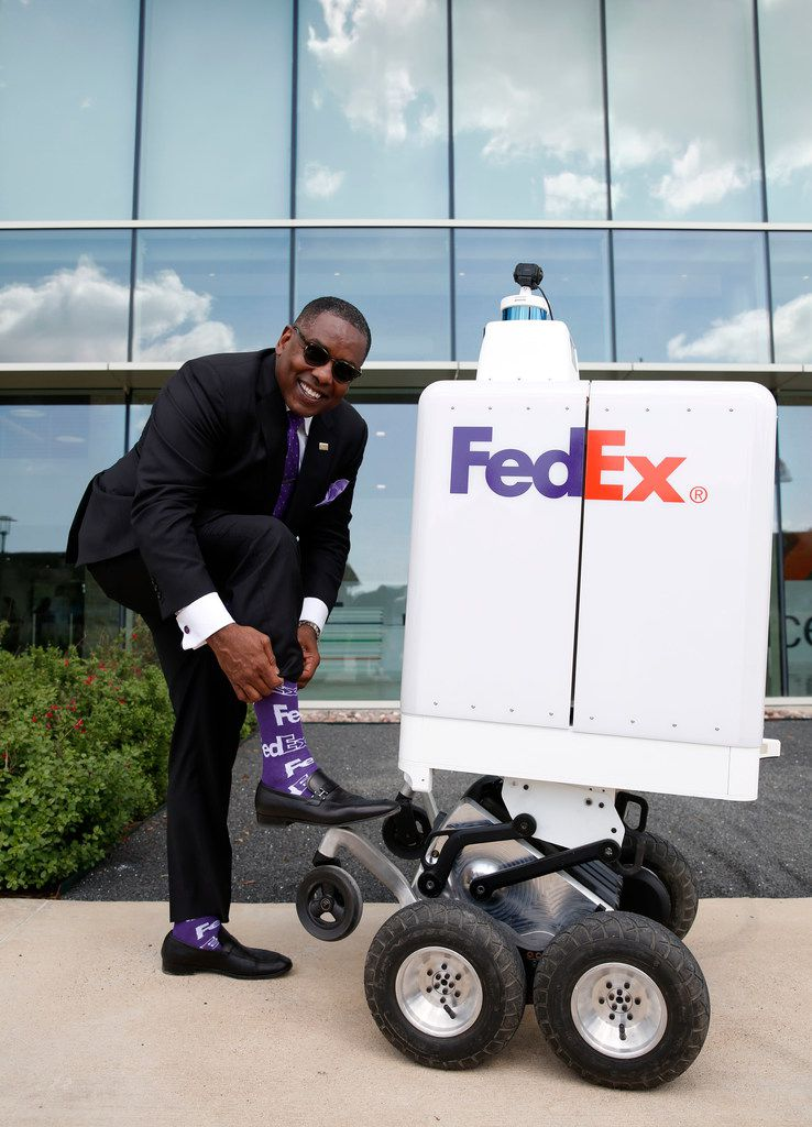 Mayor of Plano Harry LaRosiliere shows off his FedEx socks during a demonstration for the FedEx same-day bot outside the FedEx Office headquarters in Plano. He said the bot could help the city fight congestion by taking cars and trucks off the road.