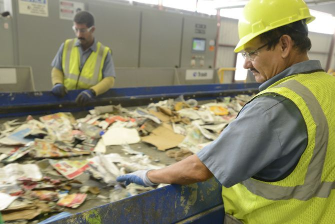 Alfredo Salgado (right) sorts paper, plastic and metal at Republic Services' new recycling complex in Fort Worth.