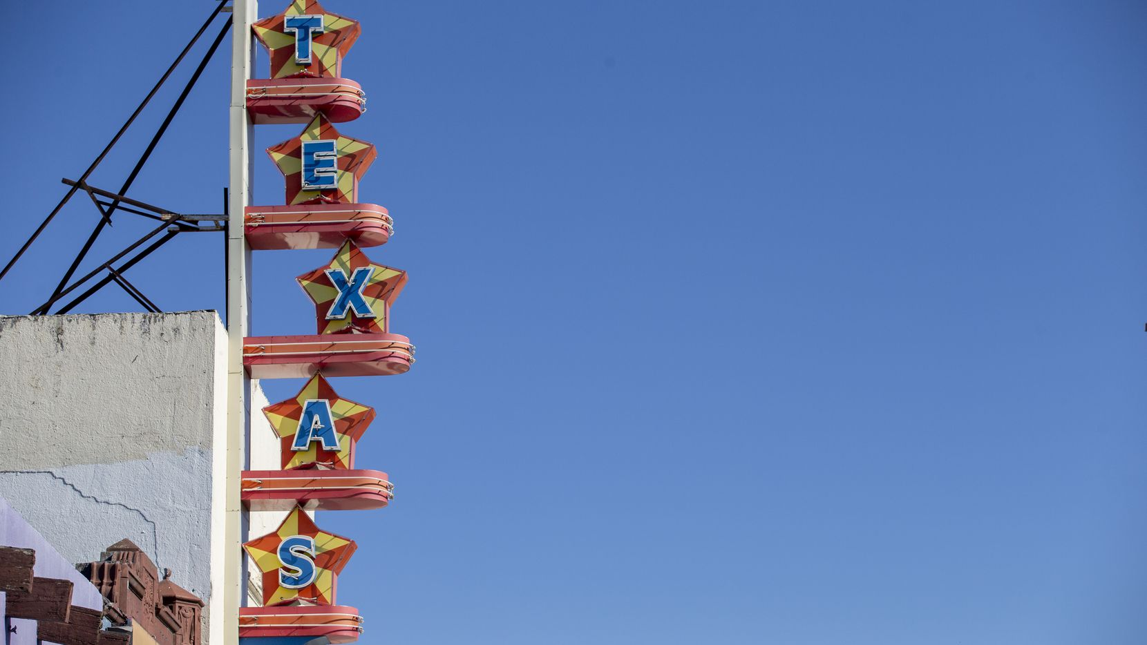 Signage for the Texas Theatre, which has been closed due to the pandemic, stands out against a bright blue sky Tuesday.