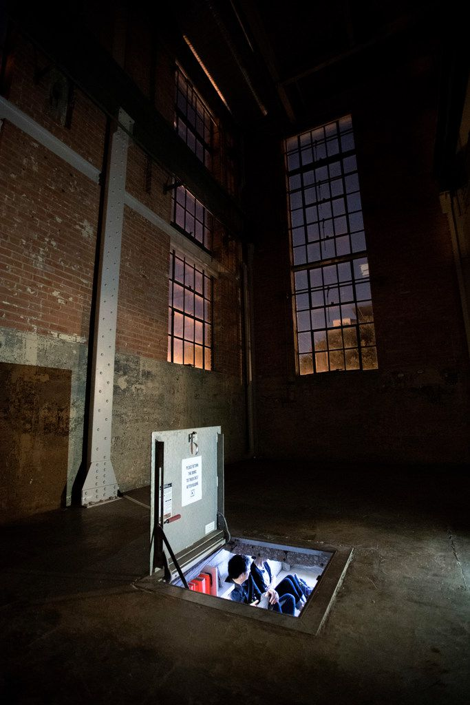 Patrons sit inside Culture Hole, a 44-square-foot underground art exhibition space with a 3.5-foot ceiling located within The Power Station art gallery, Saturday, October 14, 2017.