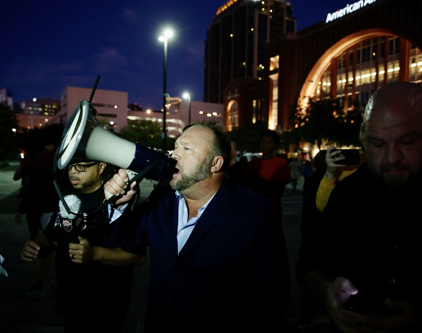 Alex Jones speaks with a bullhorn where  some of the protesters are at the site of the Keep America Great Rally for President Donald Trump at the American Airlines Center in Dallas, on Thursday, October 17, 2019.