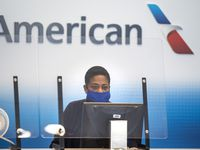 An American Airlines employee waits to help a passenger check luggage in Terminal A at DFW International Airport.