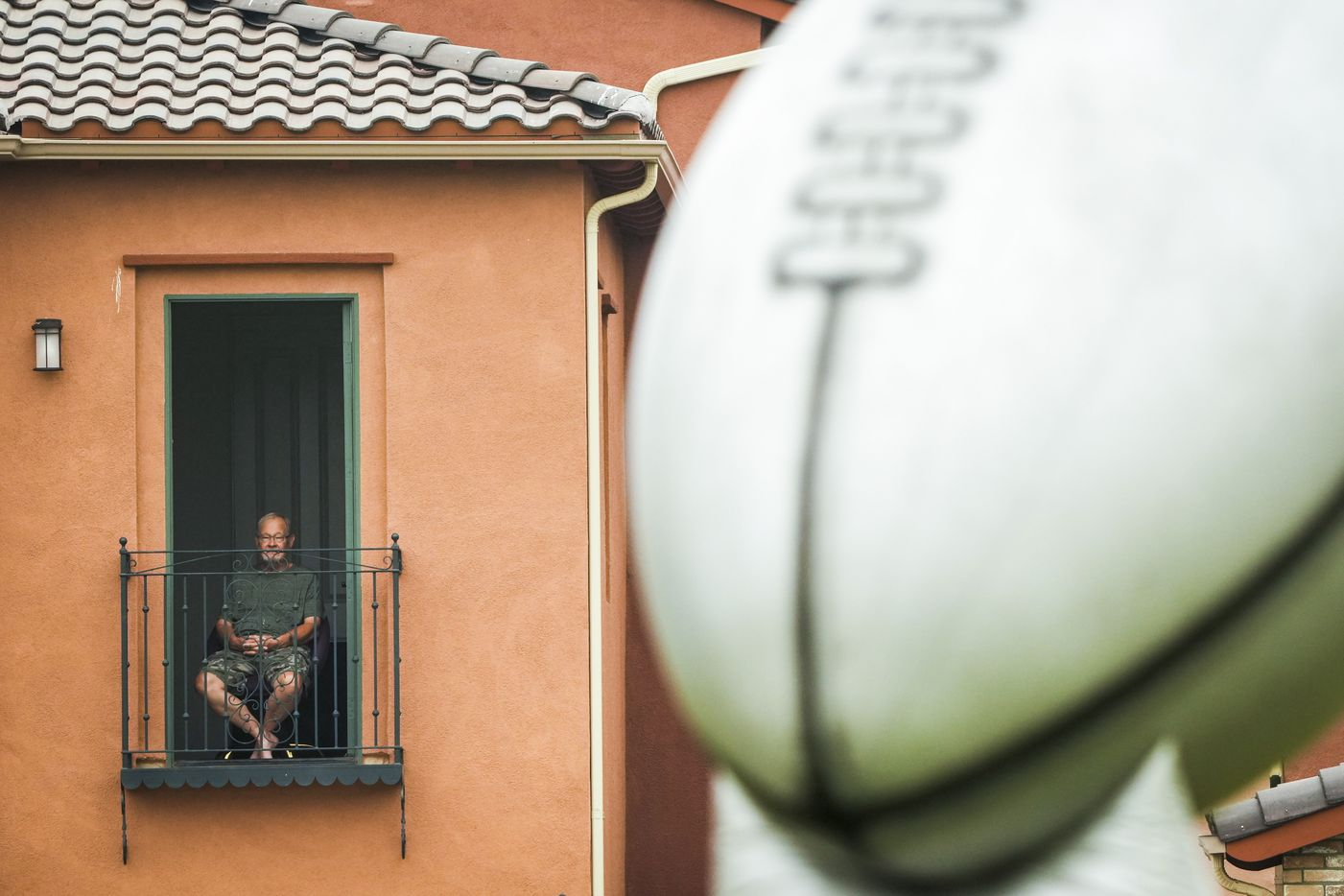 A man watches the Dallas Cowboys opening ceremonies from the balcony of a home adjacent to the facility before a practice at training camp on Saturday, July 24, 2021, in Oxnard, Calif.