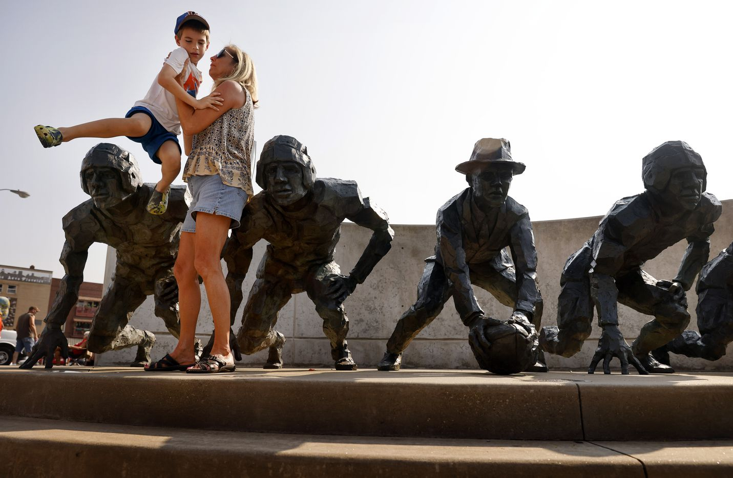 Cherrie Yerkey lifts her 7 yr-old grandson Reid Krebs off a football sculpture where they viewed  the Canton Repository Grand Parade in downtown Canton, Ohio, Saturday, August 7, 2021. The Pro Football Hall of Fame parade honored newly elected and former members of the Hall, including newcomers and former Dallas Cowboys players Cliff Harris, Drew Pearson and head coach Jimmy Johnson. (Tom Fox/The Dallas Morning News)