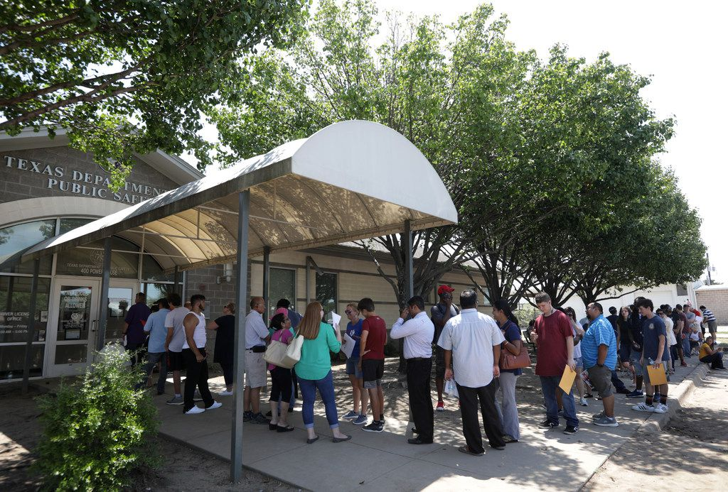 """People wait outside in the summer heat at the Texas Department of Public Safety building in McKinney, on Aug. 16, 2019. Long lines and wait times are the norm for Dallas-area drivers trying to renew their licenses at smaller Texas DPS offices such as the one in McKinney, as well as at the state's """"mega centers,"""" a year after additional staffing and other resources were devoted to the problem."""