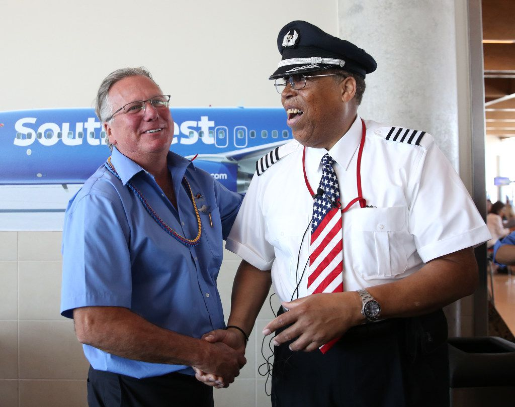 Southwest Airlines' senior pilot Lou Freeman (right), the first African-American chief pilot of a major U.S. airline, shakes hands with flight attendant Jay Giacomi before boarding his final flight at Dallas Love Field airport on Thursday.