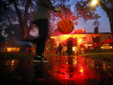 Trick-or-treaters skipped over rain puddles in the historic Swiss Avenue neighborhood of East Dallas on Oct. 31, 2018. Health experts say it's OK for kids to go trick-or-treating this Halloween.