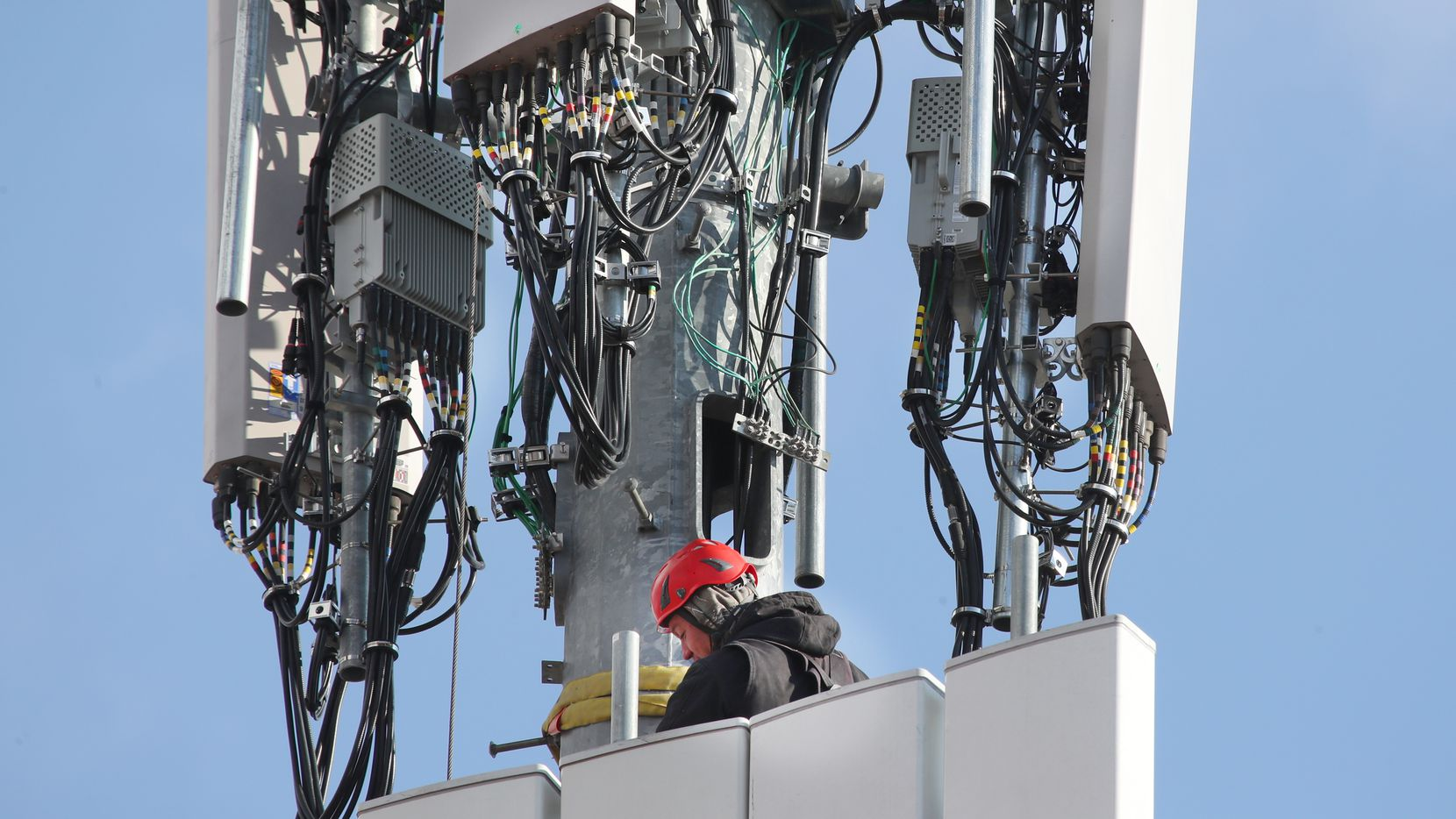 In this file photo, a worker rebuilds a cellular tower with 5G equipment for the Verizon network in Orem, Utah. (Photo by George Frey/Getty Images)