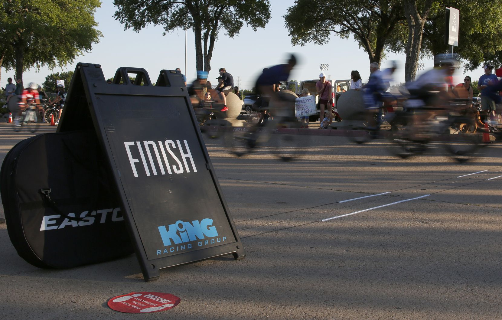 Cyclists race past the finish line during opening night for King Racing Group's season at Fair Park in Dallas on May 6, 2021.