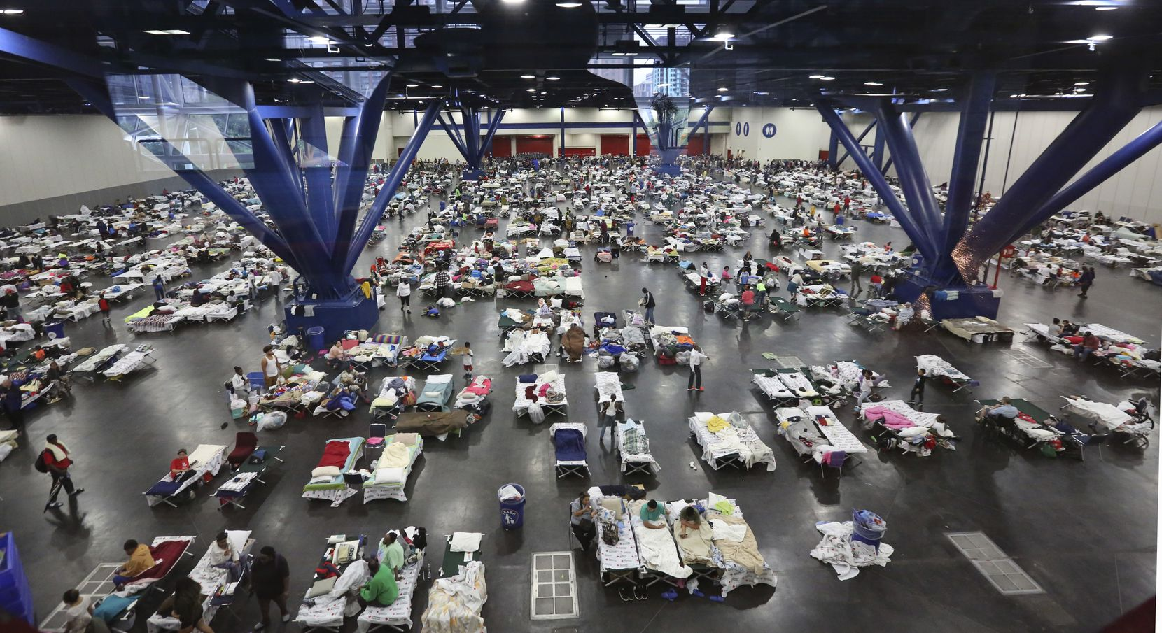 Evacuees escaping the floodwaters from Tropical Storm Harvey rest at the George R. Brown Convention Center that has been set up as a shelter in Houston, Texas, Tuesday, Aug. 29, 2017.
