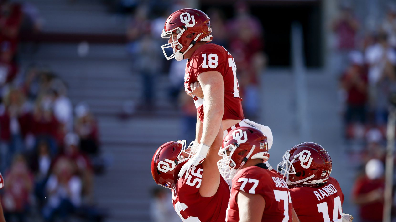 Oklahoma offensive lineman Creed Humphrey (56) lifts tight end Austin Stogner (18) after Stogner's touchdown reception against Kansas during an NCAA college football game in Norman, Okla., Saturday, Nov. 7, 2020. (Ian Maule/Tulsa World via AP)