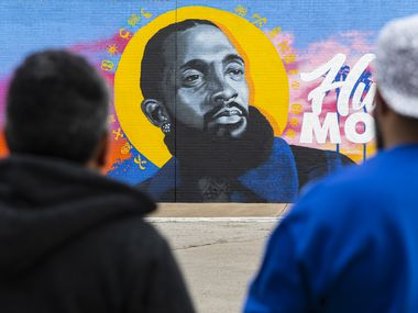 Hatziel Flores (left) and Jeremy Biggers look at their mural dedicated to the late rapper, entrepreneur and community activist Nipsey Hussle at the Glendale Shopping Center on Feb. 22, 2020 in Dallas.
