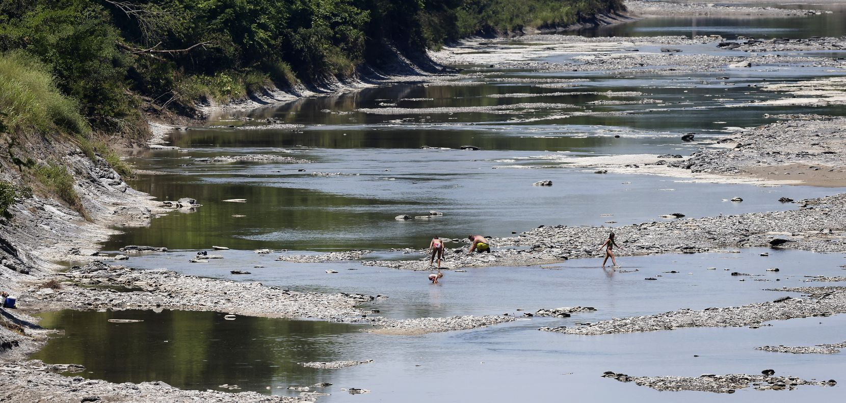A family searches for fossils in the Sulphur River where the Upper Trinity Regional Water District plans on building the Lake Ralph Hall and Leon Hurse Dam near Ladonia, Texas, Wednesday, June 16, 2021. The construction is expected to turn up more fossils near the NSR Ladonia Fossil Park on Hwy 34.  The lake will provide 54 million gallons of water per day for some 29 communities in Denton and Collin counties. The $490 million project should begin delivering water by 2025. The lake is named after Hall, who was a U.S. representative for Texas's 4th congressional district.