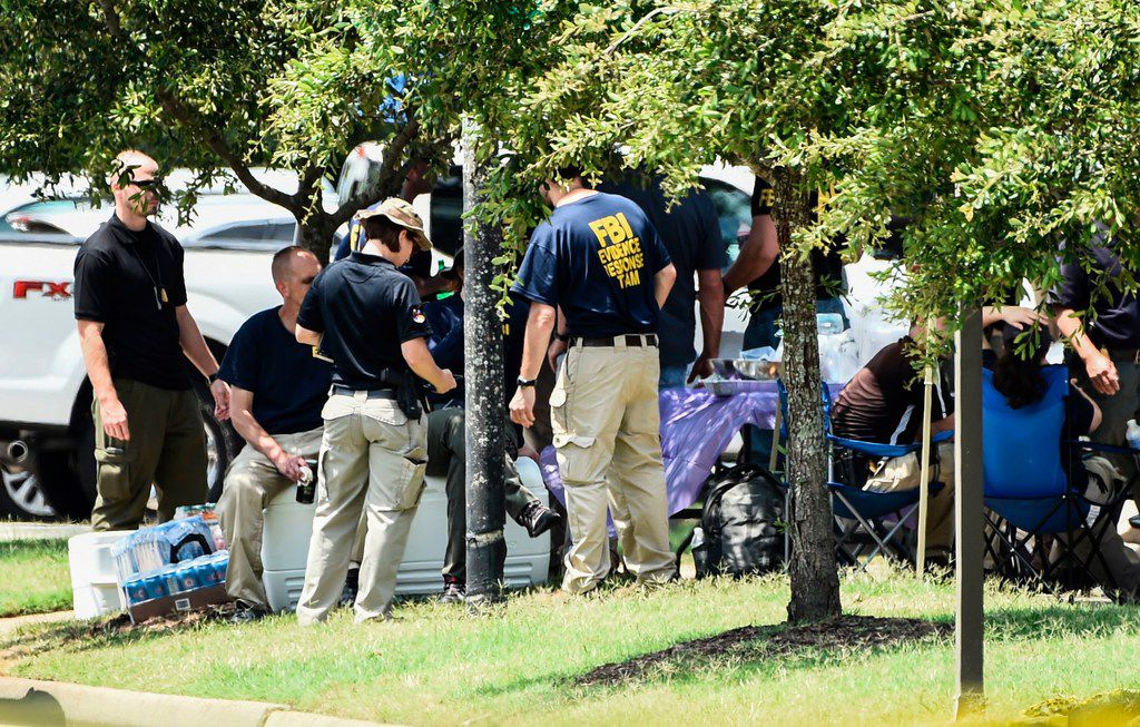 """FBI agents take a break near building number 2 at the Virginia Beach Municipal Center, the scene of the mass shooting, in Virginia, Beach, Virginia on June 1, 2019. - A municipal employee sprayed gunfire """"indiscriminately"""" in the government building complex on May 31, 2019, police said, killing 12 people and wounding four in the latest mass shooting to rock the US. (Photo by Eric BARADAT / AFP)ERIC BARADAT/AFP/Getty Images"""