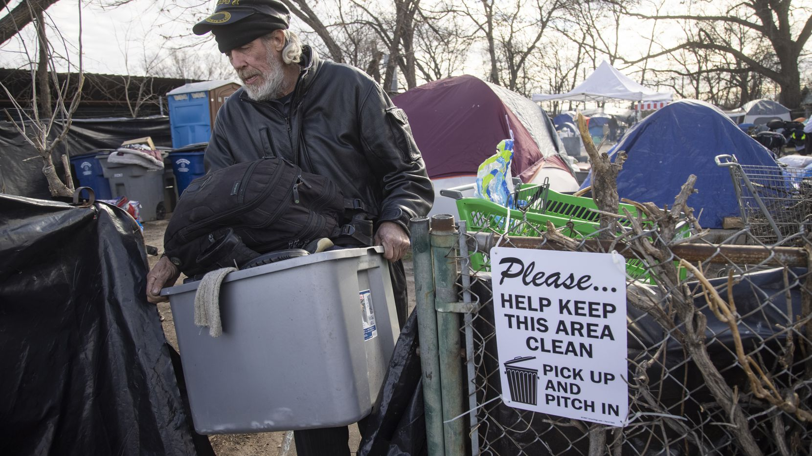 Arthur Stebbins takes some of his belongings out of Camp Rhonda, a homeless encampment located on a lot along I-45, on Friday, Feb. 5, 2021 in South Dallas. Dallas City offered the residents the ability to stay at the Hotel Miramar. Last week, city officials sent a notice to the owner of the property, Johnny Aguinaga, stating that the lot needed to be empty by Feb. 6. (Juan Figueroa/ The Dallas Morning News)