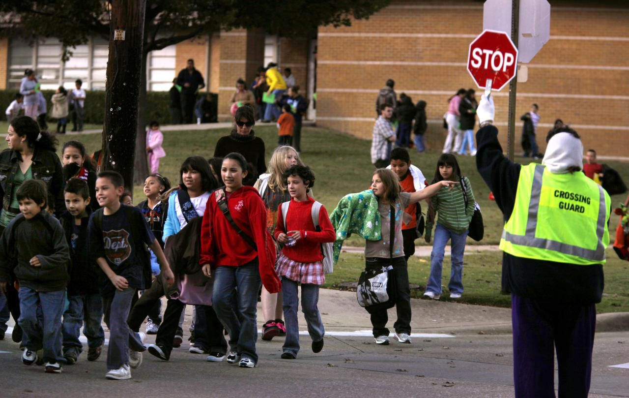 In this file photo, a crossing guard helps students safely cross the street after dismissal at Plano ISD's Mendenhall Elementary School.