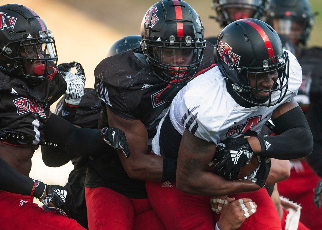 Arkansas State wide receiver Jonathan Adams Jr., front right, is swarmed by defenders after making a catch during an NCAA college football team scrimmage Saturday, Aug. 17, 2019, in Jonesboro, Ark. (Quentin Winstine/The Jonesboro Sun via AP)