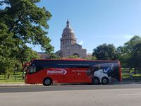 A RedCoach bus sits in front of the Texas State Capitol in Austin.