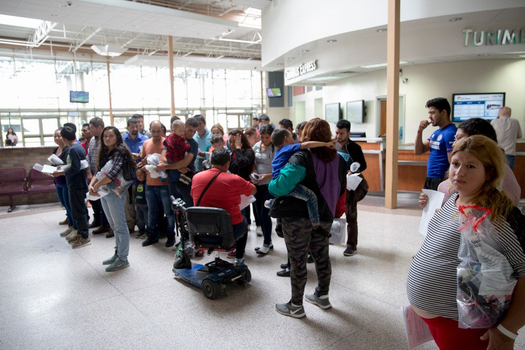 Immigrants wait to be picked up by volunteers of Catholic Charities of the Rio Grande Valley after being dropped off by ICE at the bus station in McAllen, Texas, on June 10, 2018.