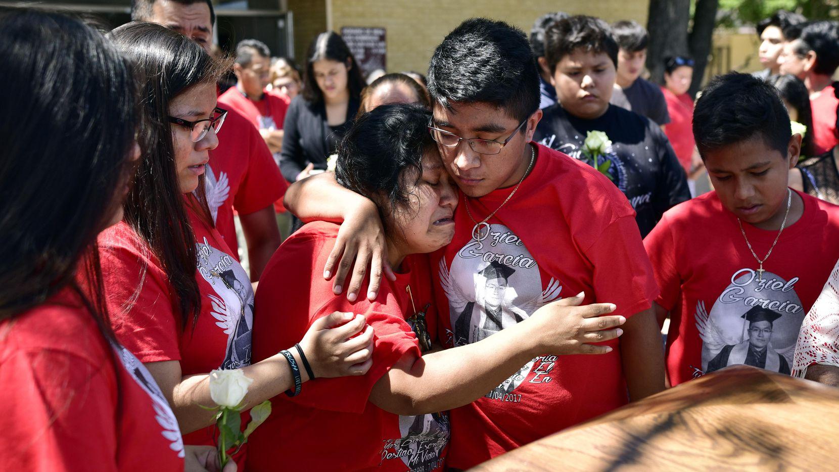 Susana García recibe el consuleo de su hijo Isaar durante el funeral de su hermano Oziel en la iglesia San Juan Diego.BEN TORRES/AL DÍA