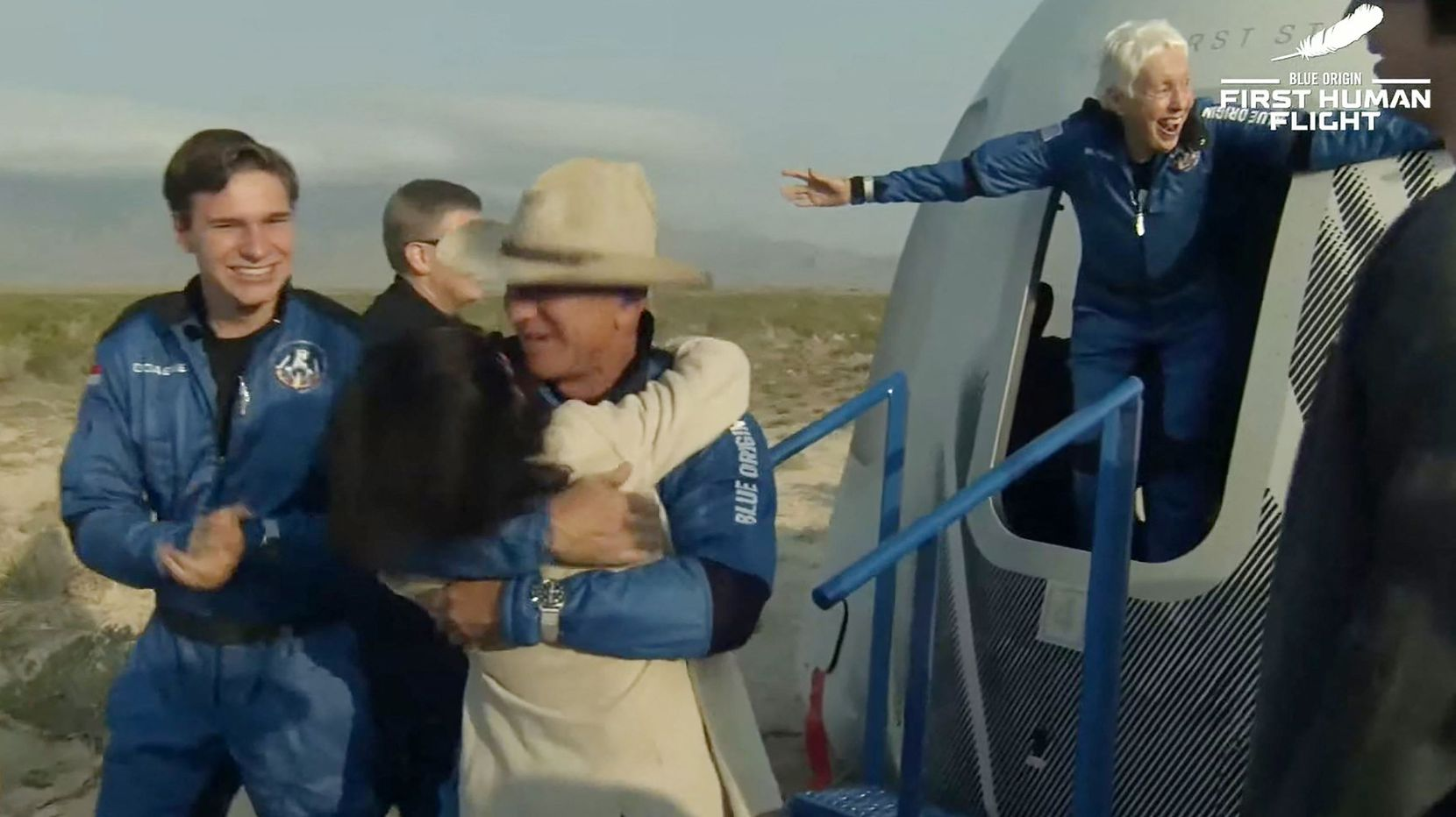 """This still image taken from video by Blue Origin shows Jeff Bezos(C), Wally Funk(R) and Oliver Daemen(L) after Blue Origin's reusable New Shepard craft capsule returned from space, safely landing on July 20, 2021, in Van Horn, Texas. - Blue Origin's first crewed mission is an 11-minute flight from west Texas to an altitude of 65 miles (106kms), and back again, to coincide with the 52nd anniversary of the first Moon landing. (Photo by Handout / BLUE ORIGIN / AFP) / RESTRICTED TO EDITORIAL USE - MANDATORY CREDIT """"AFP PHOTO / Blue Origin"""" - NO MARKETING - NO ADVERTISING CAMPAIGNS - DISTRIBUTED AS A SERVICE TO CLIENTS (Photo by HANDOUT/BLUE ORIGIN/AFP via Getty Images)"""