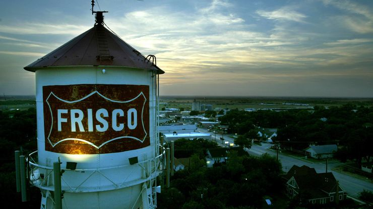 The Frisco water tower looms over downtown at dusk.