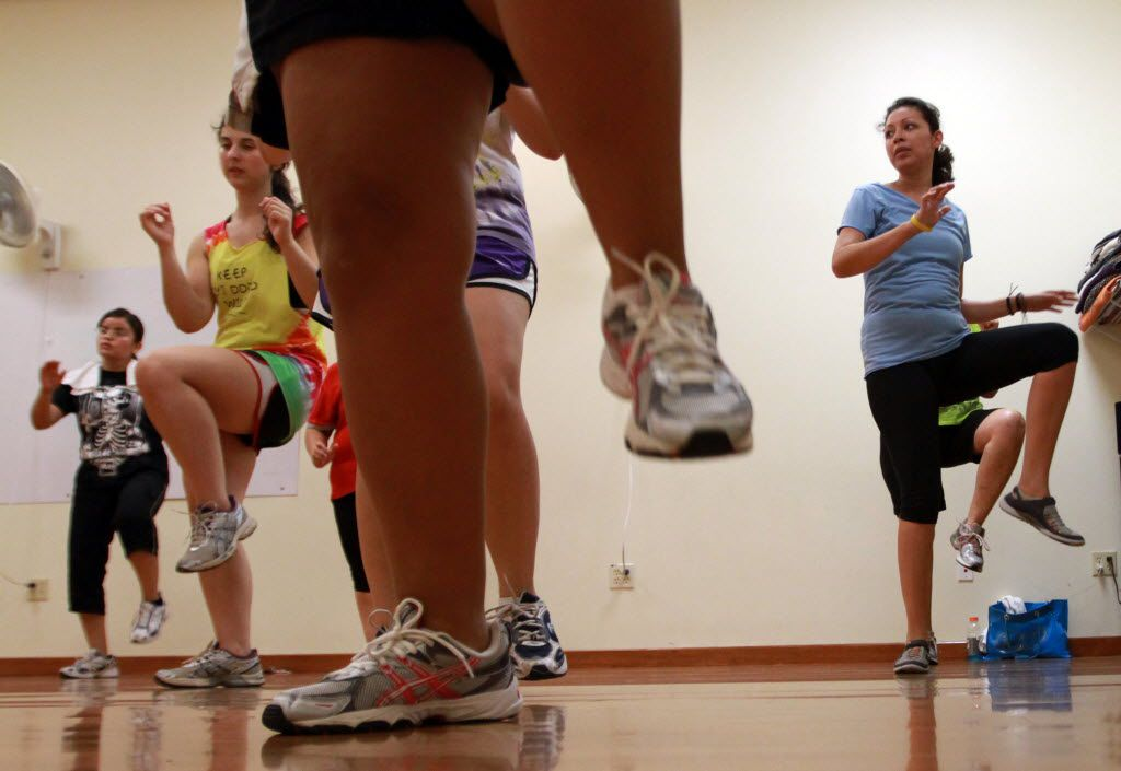 In this file image, Zumba participants can be seen exercising during a class.