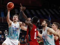 Slovenia's Luka Doncic (77) attempts a shot on Germany's Isaac Bonga (0) during the first half of play of a quarter final basketball game at the postponed 2020 Tokyo Olympics at Olympic Stadium, on Tuesday, August 3, 2021, in Tokyo, Japan.
