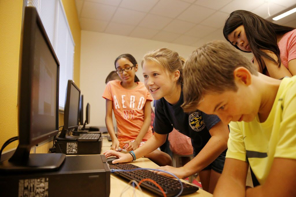 Students (from left) Samiksha Sivakumar, Mckenna Hogan and Zach Mohr, along with Isabel Tu (top right) waited for LEDs on a circuit board to react to programming changes during the 2015 Mindbender Academy summer camp at the Frisco ISD Career and Technical Education Center. (File Photo/Andy Jacobsohn)