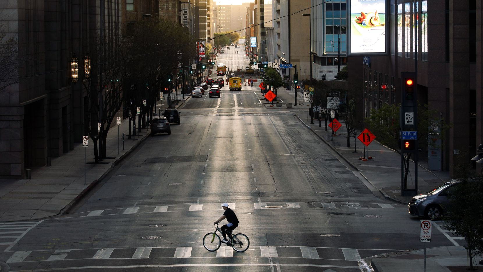 With very few cars on the street, a cyclist peddles across Elm St. in downtown Dallas, Wednesday evening, March 25, 2020.  There's less traffic than normal after Judge Clay Jenkins ordered a shelter-in-place due to coronavirus.