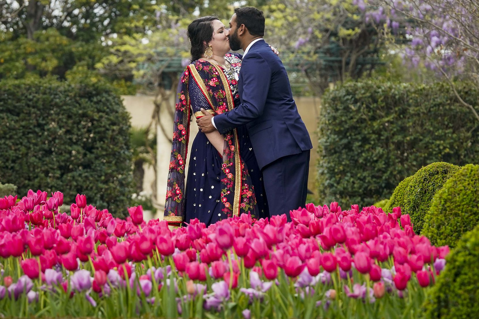 """Laura Remson and Abhishek Ravi kissed while posing for wedding photos after getting married March 19 at the nearly empty Dallas Arboretum. The couple planned a five-day, 250-person traditional wedding in India, but the pandemic changed that. """"We hope to do that eventually,"""" she said."""