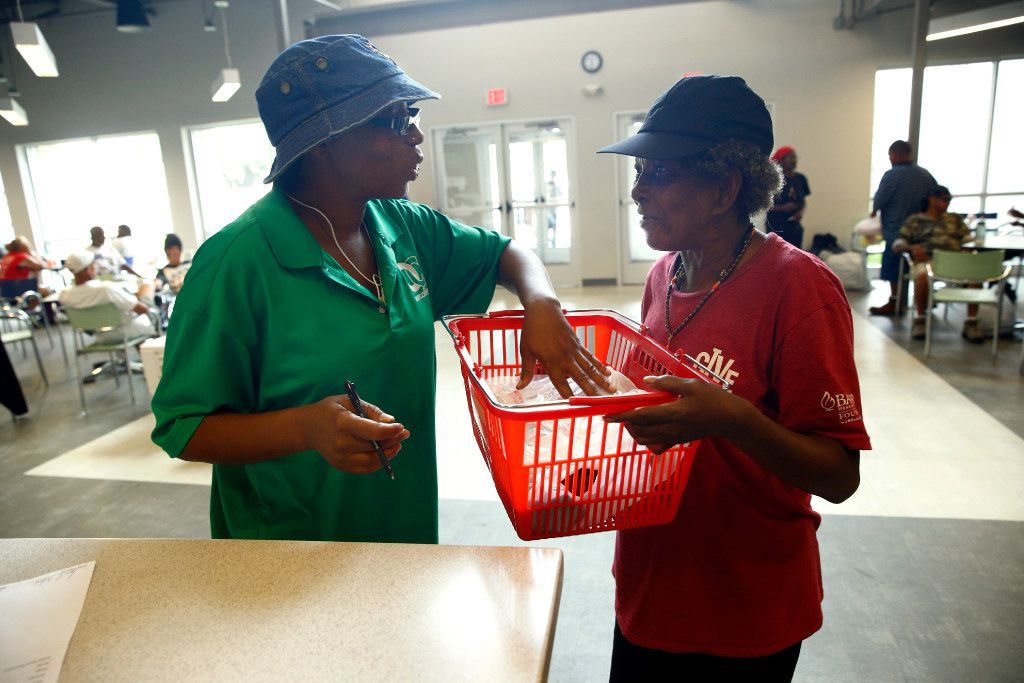 Fahdel Scriven, warehouse manager at Our Calling, hands Patricia Rucker essentials that she needs on the streets.