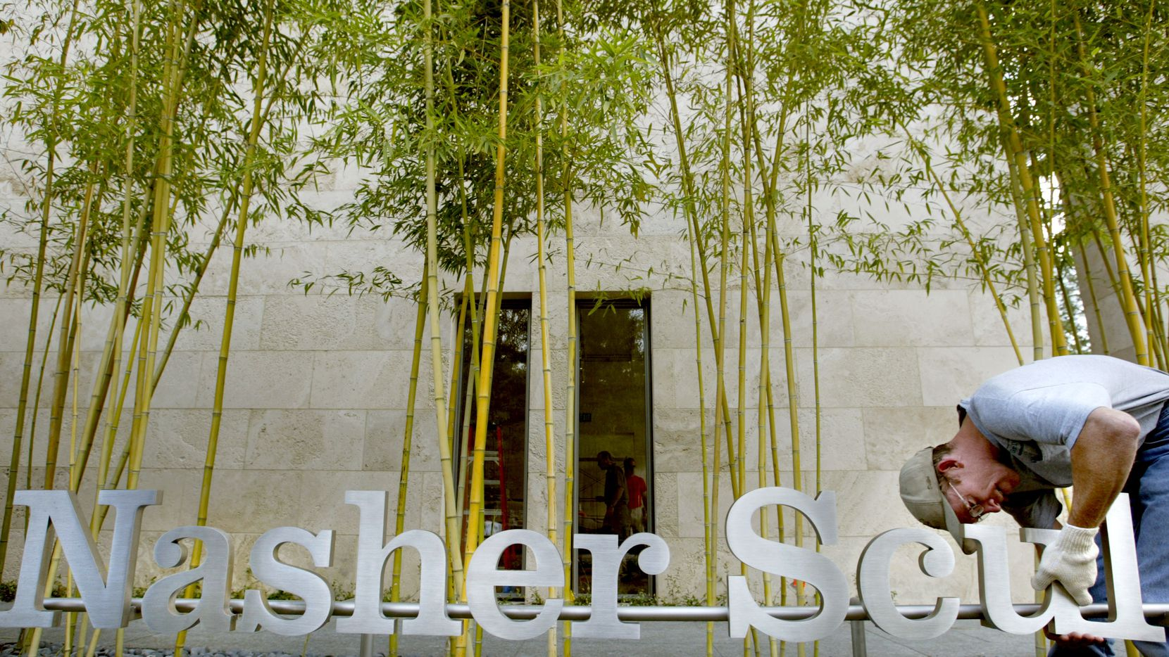 Ron Monsen installs a sign outside the Nasher Sculpture Center in downtown Dallas.