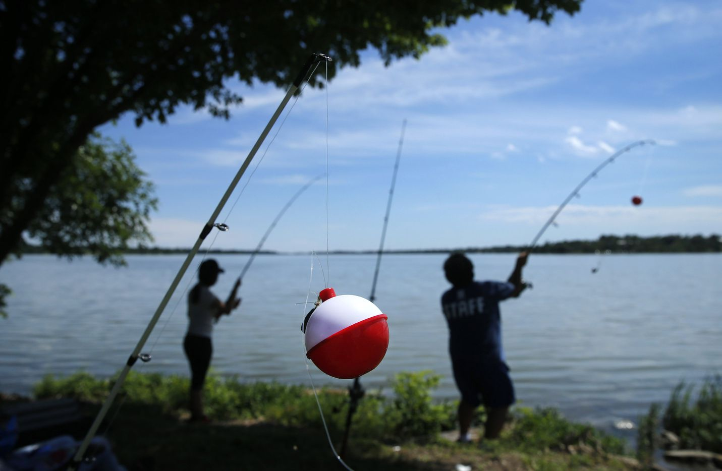 Oscar Resendiz of Dallas casts his line at White Rock Lake in Dallas as he fishes with his daughter Aleva DeLeon.